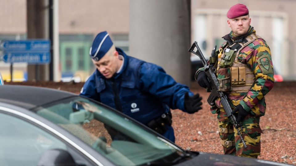 A police officer checks a car as a Belgian Army soldier patrols at Zaventem Airport in Brussels on Wednesday, March 23, 2016. (AP Photo/Geert Vanden Wijngaert)