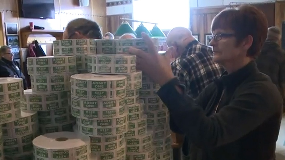 Volunteers stack rolls of new tickets for the Chase the Ace draw.