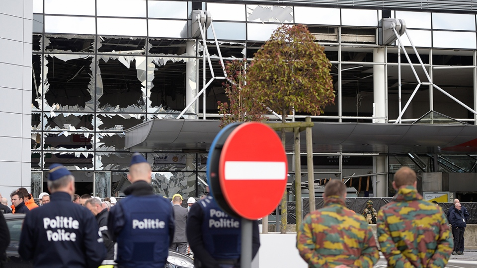Police and soldiers from the Belgian Army stand in front of blown out windows at Zaventem Airport in Brussels on Wednesday, March 23, 2016. (AP / Yorick Jansens)