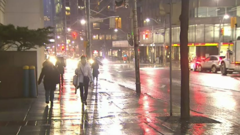 Pedestrians walk through freezing rain in downtown Toronto on Thursday, March 24, 2016