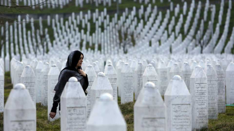 A Bosnian woman walks among gravestones at Memorial Centre Potocari near Srebrenica, Bosnia and Herzegovina on Sunday, March 20, 2016. (AP / Amel Emric)