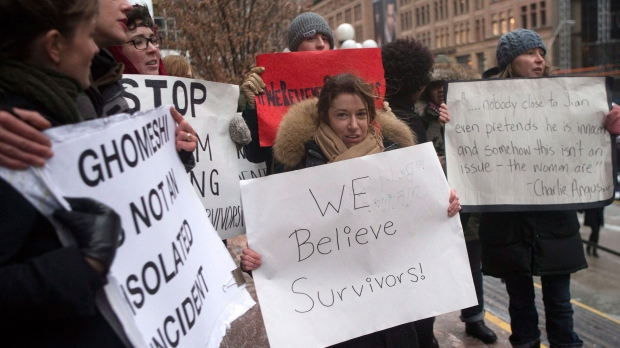 Protesters hold signs outside of the Toronto courthouse as they await a judgment in the Jian Ghomeshi sexual assault trial, on Thursday, March 24, 2016. (Chris Young / THE CANADIAN PRESS)