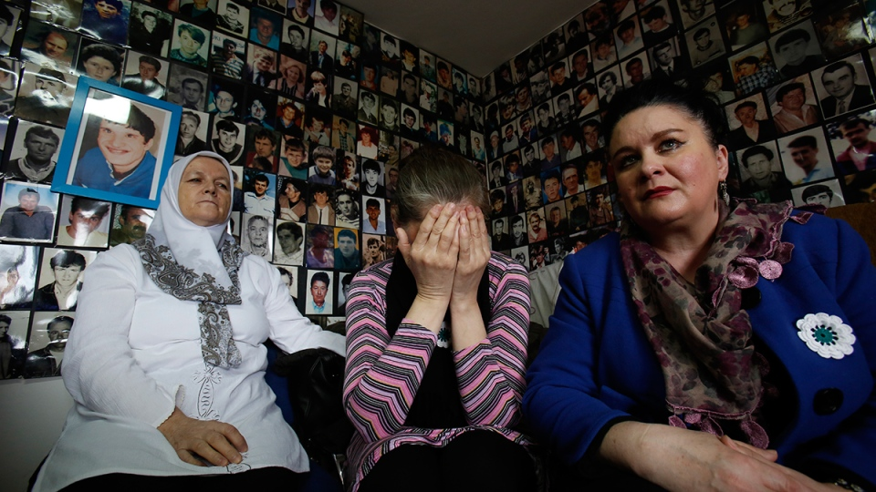 Bosnian Muslim woman who lost their family members in Srebrenica Fatima Mujic, Vasvija Kadic and Mirsada Kahriman, from left to right, react as they watch a TV broadcast of the sentencing of Radovan Karadzic at the International Criminal Tribunal for Former Yugoslavia (ICTY) in The Hague, with photos of missing Bosnian people plastered on a walls at the union of Srebrenica mothers, in Tuzla, Bosnia, on Thursday, March, 24, 2016. (AP / Amel Emric)