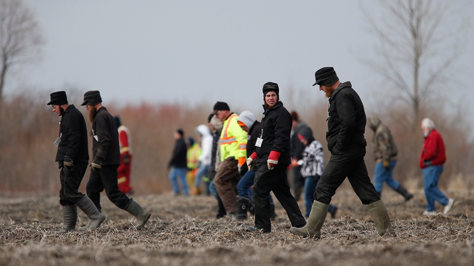 Searchers look through farmers' field and ditches hoping to find 2 year old Chase Martens near Austin, Man., on Thursday, March 24, 2016. (John Woods / THE CANADIAN PRESS)