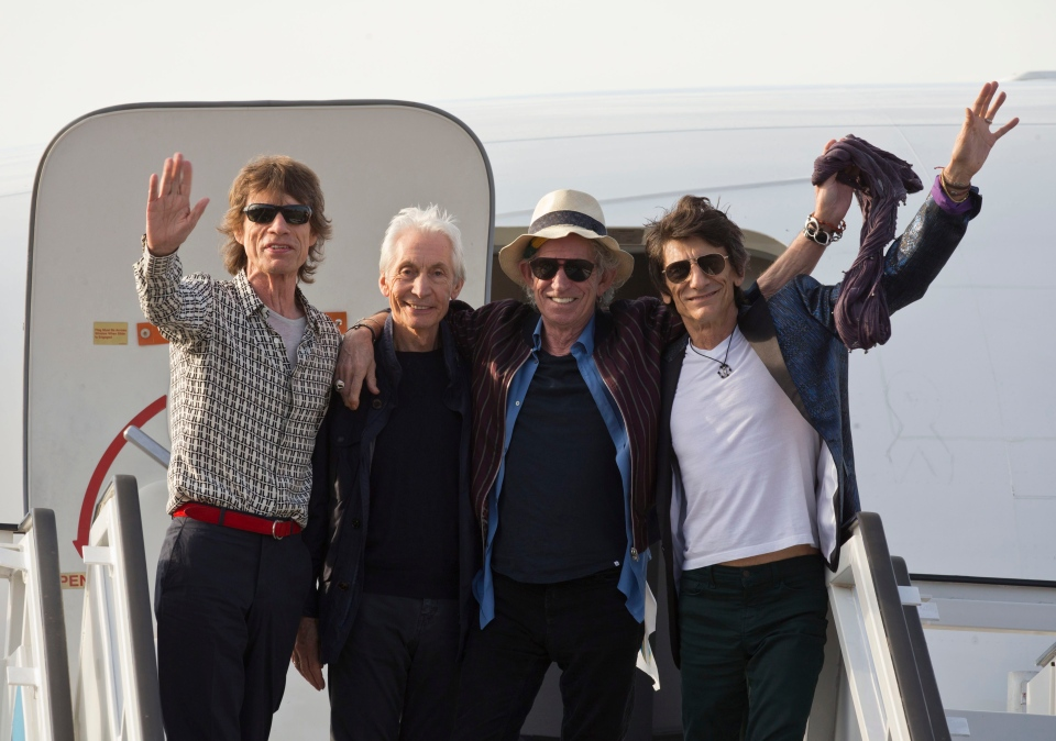 Members of The Rolling Stones, from, Mick Jagger, Charlie Watts, Keith Richards and Ron Wood pose for photos from the plane that brought them to Cuba at Jose Marti international airport in Havana, Cuba, Thursday, March 24, 2016. (AP / Ramon Espinosa)