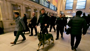 Metro-North Railroad police officers with a police dog patrol Grand Central Terminal, in New York, on March 22, 2016. (AP Photo/Richard Drew)