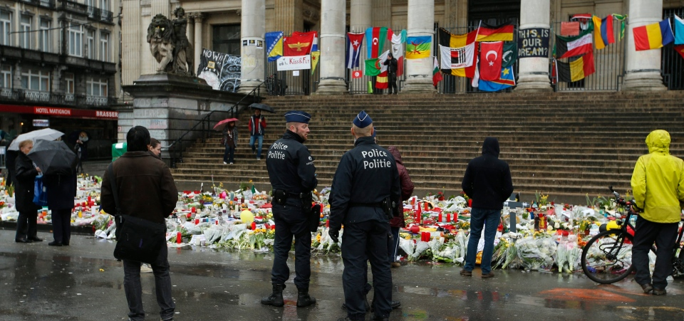 Police patrol one of the memorial sites for the victims of the recent attacks in Brussels at the Place de la Bourse in Brussels, Friday, March, 25, 2016. (AP / Alastair Grant)