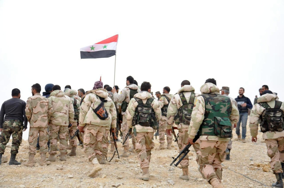 In this photo released by the Syrian official news agency SANA, Syrian soldiers gather around a Syrian national flag in Palmyra, Syria, Sunday, March 27, 2016. (SANA via AP)
