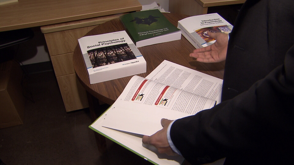 Rajiv Jhangiani shows off the open textbooks he uses for his courses. (CTV)