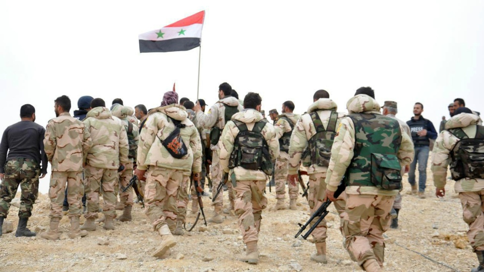 Syrian soldiers gather around a Syrian national flag in Palmyra, Syria on Sunday, March 27, 2016. (SANA)
