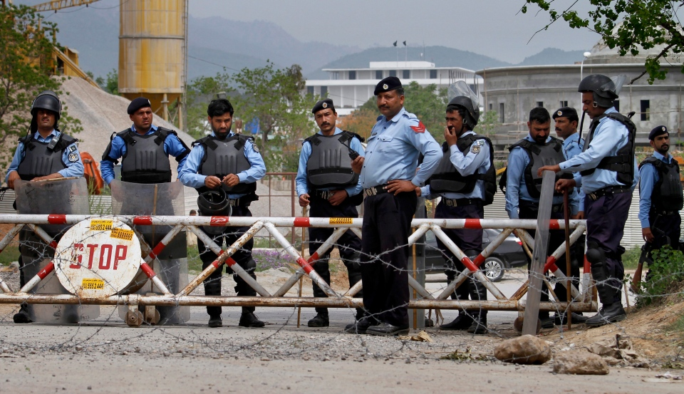 Pakistani police officers stand guard on a road leading to the Parliament building, where supporters of a religious group are holding a sit-in, in Islamabad, Pakistan, Monday, March 28, 2016. (AP / Anjum Naveed)