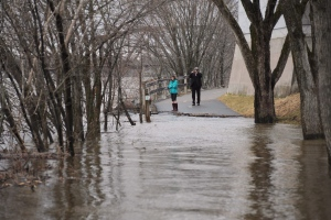 In this file photo, people walk to edge of the flooded trail in Fredericton on Thursday, April 23, 2015. (Stephen MacGilivray/THE CANADIAN PRESS)