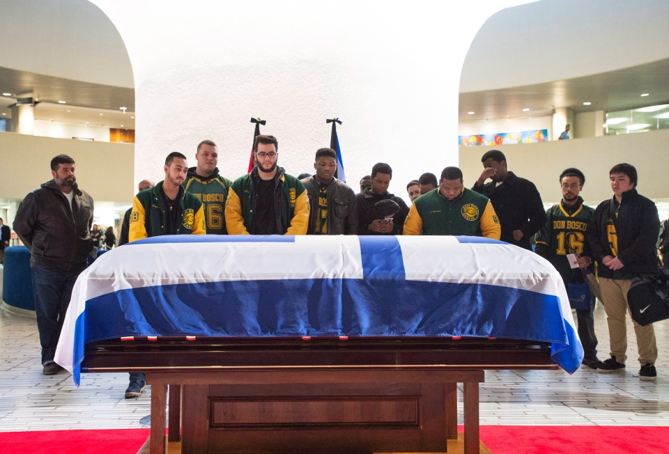 Members of the Don Bosco football team pay their respects to former Toronto mayor Rob Ford's casket at city hall on Monday, March 28, 2016. (Nathan Denette / THE CANADIAN PRESS)