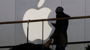 A woman using a phone walks past Apple's logo near its retail outlet in Beijing, Dec. 23, 2013.  (AP / Ng Han Guan)