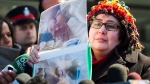 Jennifer Neville-Lake cries as she shows photographs of her three children and father who were killed in a horrific crash by drunk driver Marco Muzzo at the courthouse in Newmarket, Ont., on Tuesday, March 29, 2016. (Nathan Denette / THE CANADIAN PRESS)