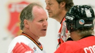 Former NHL hockey great Mark Napier, left, speaks with Canadian rocker Tom Cochrane, right, as Jim Cuddy, of the band Blue Rodeo, skates by at the Juno Cup at the Juno celebrations in Calgary Friday, April 4, 2008. (THE CANADIAN PRESS / Jonathan Hayward)