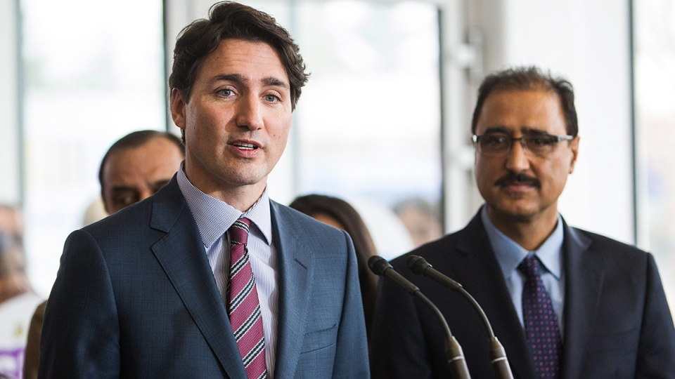 Prime Minister Justin Trudeau speaks to the media as Amarjeet Sohi, Member of Parliament for Edmonton Mill Woods, right, looks on during a stop at the Mill Woods branch of Edmonton Public Library in Edmonton, on Wednesday, March 30, 2016. (Codie McLachlan / THE CANADIAN PRESS)