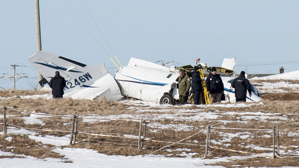 National Transportation Safety Board inspectors go over the wrecked airplane in a field in Havre-aux-Maison, Que., Wednesday, March 30, 2016. (David Noel / THE CANADIAN PRESS)
