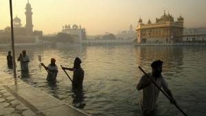 Indian Sikh devotees clean the tank early in the morning at the Golden Temple, on the birth anniversary of Guru Nanak, the first Sikh Guru in Amritsar, India on Nov. 17, 2013. (AP / Sanjeev Syal)