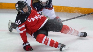 In this file photo, Canada's Blayre Turnbull of Stellarton, N.S., left, fights for control of the puck with United States' Paige Savage during the second period of the gold medal game of the Four Nations Cup women's hockey tournament in Kamloops, B.C. Saturday, Nov. 8, 2014. (THE CANADIAN PRESS / Jonathan Hayward)