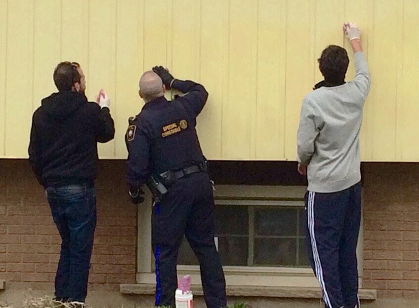 A spray-painted racial slur is removed from a home on Hazel Street in Waterloo. (@SpottedLaurier / Twitter)