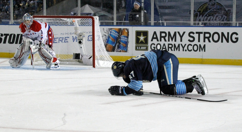 In this Jan. 1, 2011, photo, Pittsburgh Penguins' Sidney Crosby, right, crawls on the ice after being injured in the second period of the NHL Winter Classic outdoor hockey game in Pittsburgh. Washington Capitals goalie Semyon Varlamov is at left. (AP / Keith Srakocic)