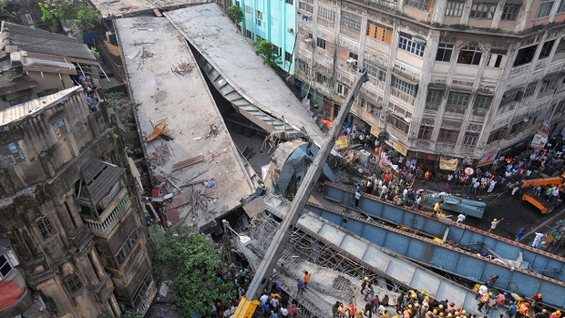 Locals and rescue workers clear the rubble of a partially collapsed overpass in Kolkata, Thursday, March 31, 2016. (AP Photo)