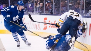 Buffalo Sabres' left wing Johan Larsson (22) takes out Toronto Maple Leafs' defenceman Frank Corrado (20) as Maple Leafs' centre Frederik Gauthier (54) looks for the loose puck during first period NHL hockey action in Toronto on Saturday, March 19, 2016. (THE CANADIAN PRESS/Nathan Denette)