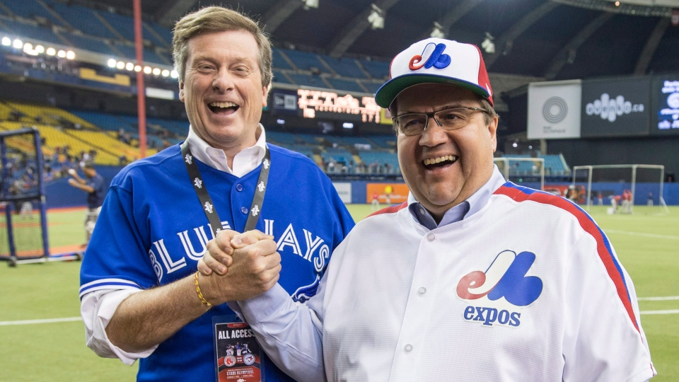 Montreal Mayor Denis Coderre, right, shares a laugh with Toronto counterpart John Tory prior to the Blue Jays facing the Boston Red Sox in a spring training baseball game Saturday, April 2, 2016 in Montreal. (THE CANADIAN PRESS/Paul Chiasson)