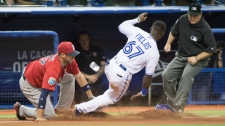 Toronto Blue Jays' Roemon Fields is tagged out stealing third by Boston Red Sox third baseman Travis Shaw as umpire Toby Basner makes the call during ninth inning spring training baseball game Friday, April 1, 2016 in Montreal. THE CANADIAN PRESS/Paul Chiasson