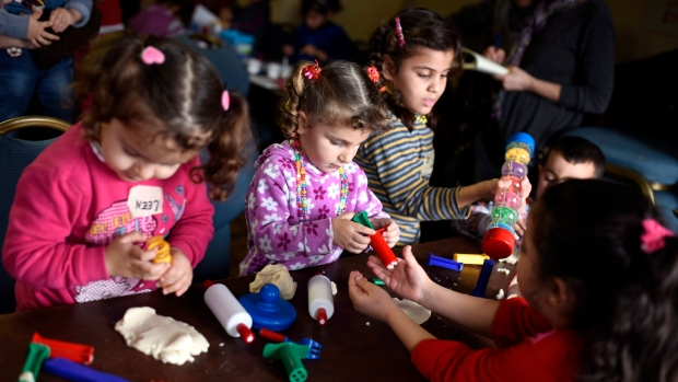 Syrian refugee children play with playdough during a playgroup organized by Ottawa Community Health Centres to provide early childhood education development services on Wednesday, March 9, 2016 in Ottawa. (Justin Tang / THE CANADIAN PRESS)