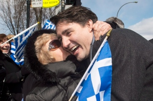 Prime Minister Justin Trudeau is hugged by a member of the crowd as he attends the Greek Independence Day parade in Montreal, Sunday, April 3, 2016. (THE CANADIAN PRESS / Graham Hughes)