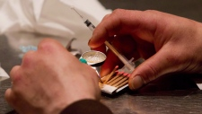 A man prepares heroin to be injected