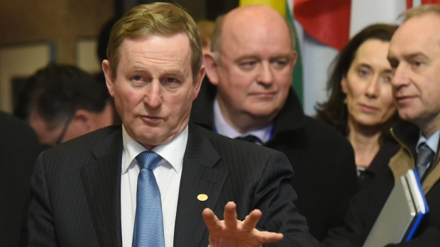 In this Friday, Feb. 19, 2016 file photo, Irish Prime Minister Enda Kenny, left, as he speaks with members of his delegation at the conclusion of an EU summit in Brussels. (AP Photo / Geert Vanden Wijngaert, File)