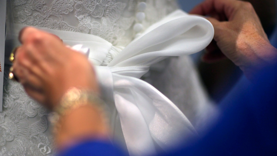 A woman ties a bow on a wedding gown at Alfred Angelo Bridal, in in Cherry Hill, N.J., on Wednesday, Nov. 11, 2015. (AP Photo/Mel Evans)