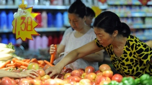 Chinese shoppers select vegetables at a market in Hefei, east China's Anhui province on July 9, 2012. (AFP PHOTO)