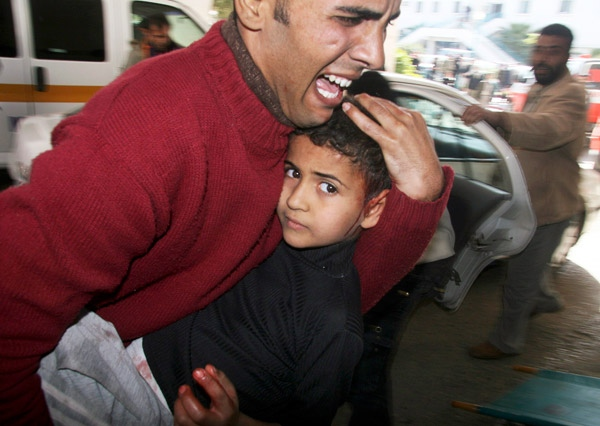 A Palestinian man carries his son, wounded in Israeli army operations, into Shifa hospital in Gaza City, Wednesday, Jan. 7, 2009. (AP / Ashraf Amra)