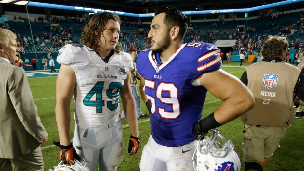 In this Sept. 27, 2015, photo, Miami Dolphins linebacker Zach Vigil (49) and Buffalo Bills linebacker A.J. Tarpley (59) talks at the end of an NFL football game in Miami Gardens, Fla. Bills linebacker A.J. Tarpley cites two concussions he sustained last year as the reason he has elected to retire from football after just one season. (AP Photo/Wilfredo Lee)