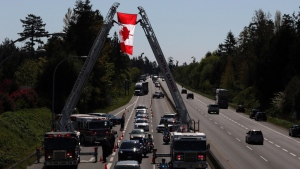 Police from across Vancouver Island stand along the Pat Bay highway as Central Saanich Fire Department raises the Canadian flag over the body of RCMP Const. Sarah Beckett as she's taken to the airport in Saanich, B.C., Thursday, April 7, 2016. (THE CANADIAN PRESS/Chad Hipolito)