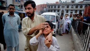 A man helps an injured boy to a hospital after an earthquake hit Peshawar, Pakistan, Sunday, April 10, 2016. A powerful earthquake rattled Pakistan's capital and other cities across the country on Sunday, causing panic among people but with no immediate reports of casualties or major damages. (AP Photo/Mohammad Sajjad)