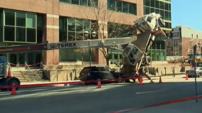 One worker is dead and another injured after the crane overturned Sunday morning.