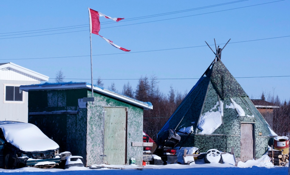 The remains of a Canadian flag can be seen flying over a building in Attawapiskat, Ont. on November 29, 2011. (Adrian Wyld / The Canadian Press)