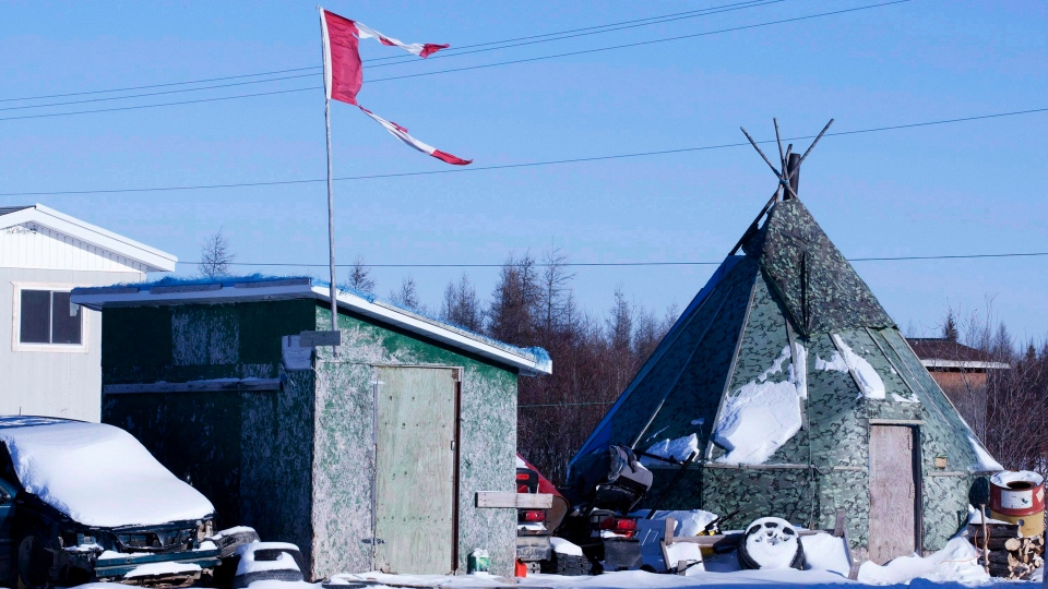 A tattered Canadian flag flies over a building in Attawapiskat, Ont., on November 29, 2011. THE CANADIAN PRESS/Adrian Wyld