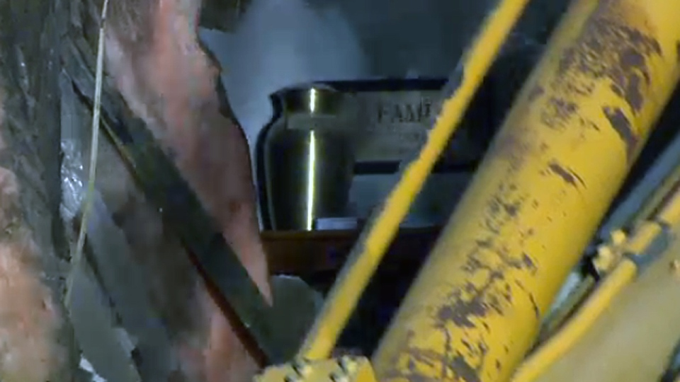 An urn containing ashes sits in a building that was demolished Sunday night