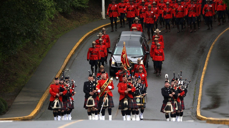 RCMP officers, municipal police departments, EMS and uniformed enforcement agencies march side by side along the Old Island Highway towards the Q Centre arena for the regimental funeral service for Const. Sarah Beckett in Colwood, B.C. on April 12, 2016. (THE CANADIAN PRESS/Chad Hipolito)