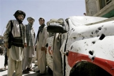 Afghan men stand near a damaged vehicle after a suicide attack at a market in Gardez, the provincial capital of Paktia province, east of Kabul, Afghanistan on Sunday, May 20, 2007. (AP Photo / Musadeq Sadeq)