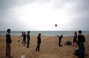 "In this April 12, 2016 file photo, Palestinian children play football on the beach during a rainy day in Gaza City. The United Nations' top  Middle East envoy warned the Security Council Wednesday that unless ""radically more"" is done, fragile peace in Gaza is in jeopardy. (Khalil Hamra/The Associated Press)"