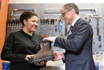 Alberta President of Treasury Board and Minister of Finance Joe Ceci donates work boots to Women Building Futures student Kim Brertton during a pre budget photo opportunity in Edmonton Alta, on Monday April 13, 2016. (Jason Franson / THE CANADIAN PRESS)