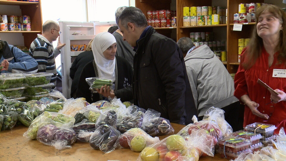 Ahamed Hamami talks with an Arabic interpreter at the Gloucester Emergency Food Cupboard in Ottawa, April 13, 2016