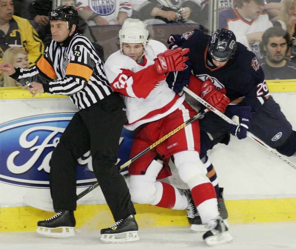 Edmonton Oilers' Brad Winchester, right, checks Detroit Red Wings' Robert Lang into referee Dean Warren during the second period of NHL Western Conference quarterfinals hockey action at Edmonton's Rexall Place on April 27, 2006. (The Canadian Press / John Ulan)